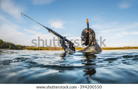 Man with speargun going to hunt in the fresh water lake