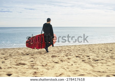 Man with stand up paddle board or sup on the beach. - stock photo