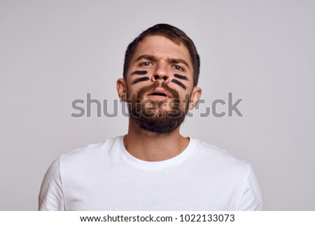 man with stripes on his face on a light background, sports