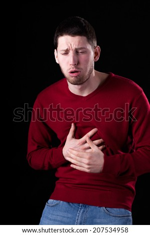 Man with strong cough isolated on black - stock photo