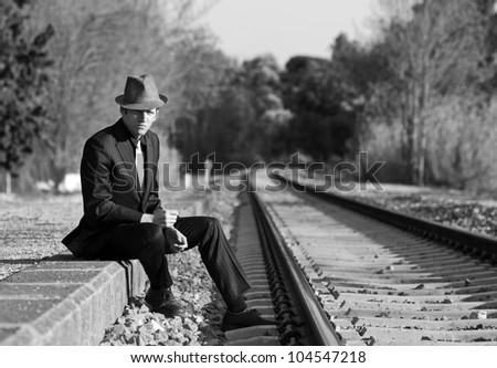 Man with suit and hat sitting beside the railway - stock photo