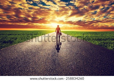 Man with suitcase and hat on long straight road towards sunset sky. Travel, business, destination, adventure concepts. - stock photo