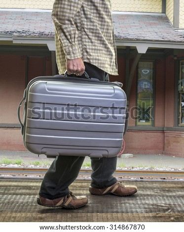 Man with suitcase at a train station - stock photo