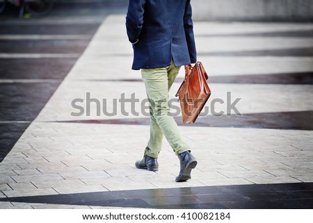 Man with suitcase, on way home from work. Focus on bag. - stock photo