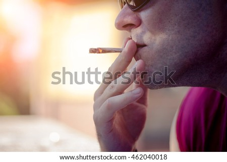 Man with sunglasses smoking mariuana cigarette outside on sunset