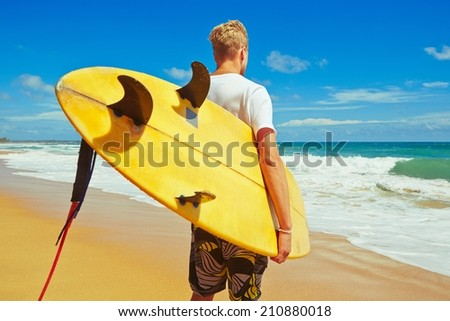 Man with surfboard on the beach at sunset.   - stock photo