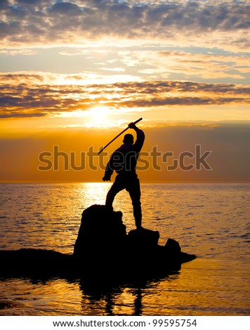 Man with sword near the sea at sunset time - stock photo