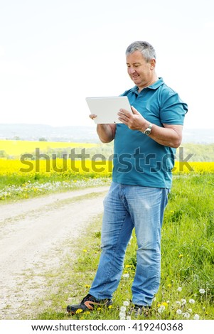 Man with tablet PC on the field