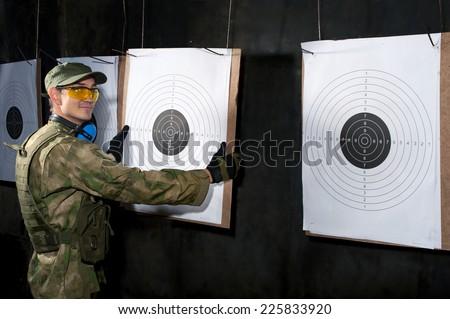 Man with target in shooting range - stock photo