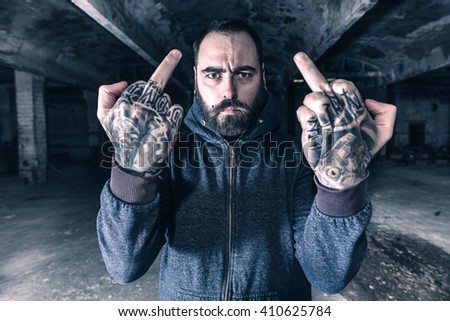 Man with tattoos on his hands showing middle fingers,selective focus  - stock photo