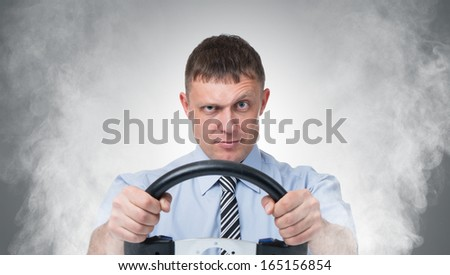 Man with the wheel in the smoke, auto concept  - stock photo