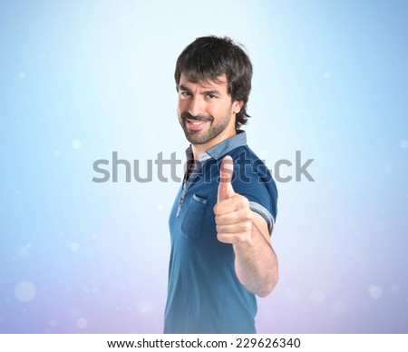 Man with thumb up over blue background - stock photo