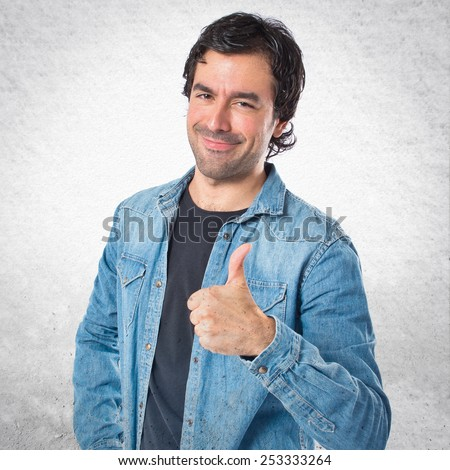 Man with thumb up over textured background - stock photo