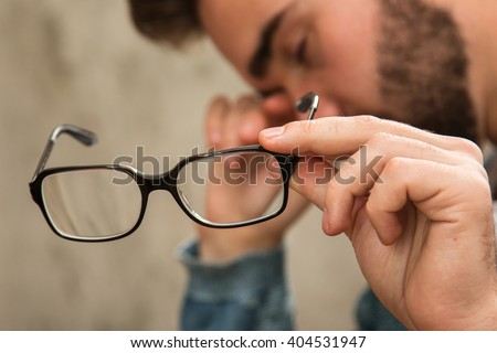 Man with tired eyes after long work holding his eyeglasses