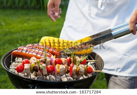 Man with tongs cooking on a back yard barbecue. - stock photo