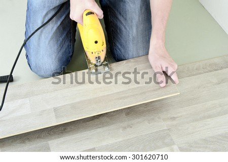 Man with Tools to Laying Laminate. Working time - stock photo