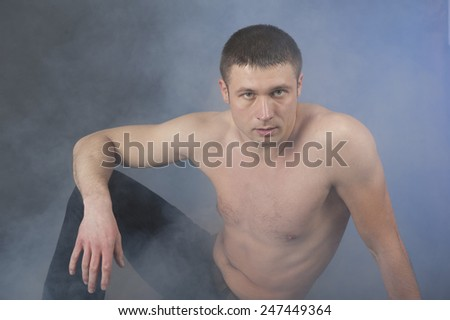 Man with torso sits in smoke - stock photo