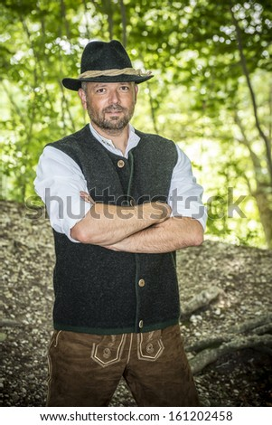 Man with traditional Bavarian costume is standing in a forest
