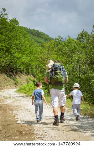 Man with two boys hiking in the forest