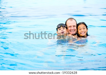 Man with two children having fun in the tropical swimming pool - stock photo