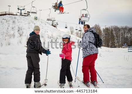 Man with two children look backwards while ski to cableway in winter day at ski resort. - stock photo