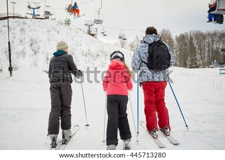 Man with two children ski to cableway in winter day at ski resort, rear view.