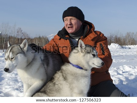 Man with two dogs of breed husky in the winter on the snow