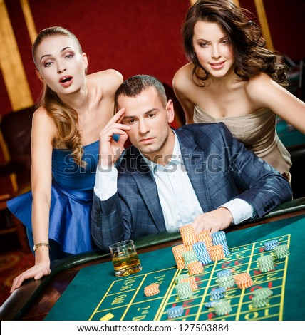 Man with two girls playing roulette at the casino. Addiction to the gambling - stock photo