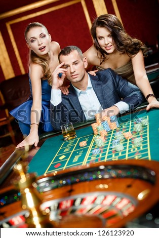 Man with two girls playing roulette at the casino club. Addiction to the gambling - stock photo