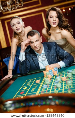 Man with two girls playing roulette at the gambling house. Addiction to the gambling - stock photo