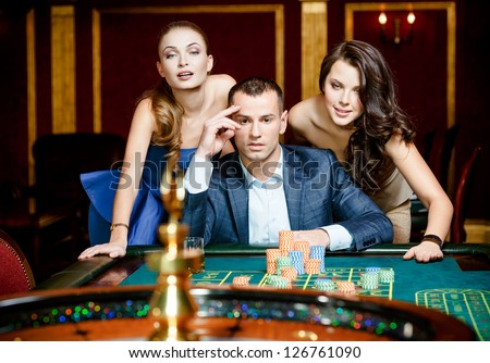 Man with two ladies playing roulette at the casino. Addiction to the gambling - stock photo