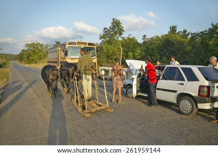 Man with two oxen pulling sled past broken down Fiat car in the Valle de Vinales, in central Cuba