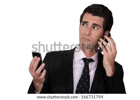 Man with two phones - stock photo