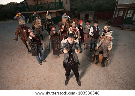 Man with two pistols backed up with a gang in old west costumes - stock photo