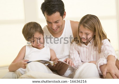 Man with two young children sitting in bed reading a book and smiling