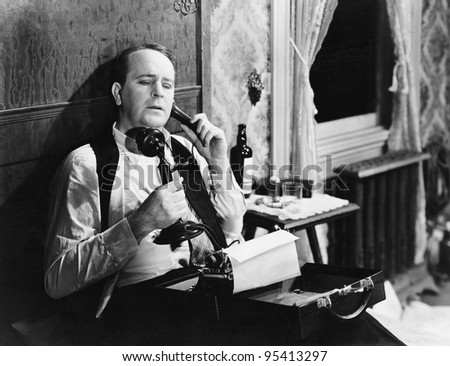 Man with typewriter talking on phone