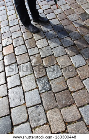 Man with umbrella and his shadow on old cobblestoned street in Nuremberg, Germany. - stock photo