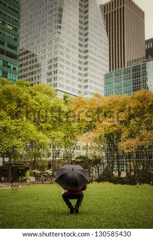 Man with umbrella in Bryant Park, among skyscrapers, New York City - stock photo