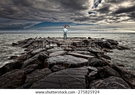 man with umbrella on sea rock bad weather - stock photo
