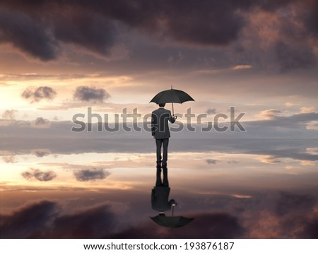 Man with umbrella on the beach watching the sunset