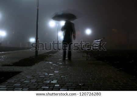 man with umbrella walking in the light of lanterns in the night park - stock photo