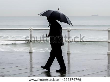 man umbrella walking through city stock photo edit now 229374796