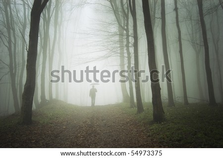 man with umbrella walking to light in a misty forest - stock photo