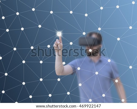 Man with VR glasses pushing on a touch screen interface