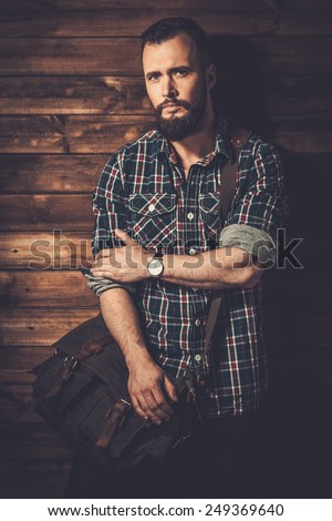 Man with wearing checkered  shirt and messenger bag - stock photo