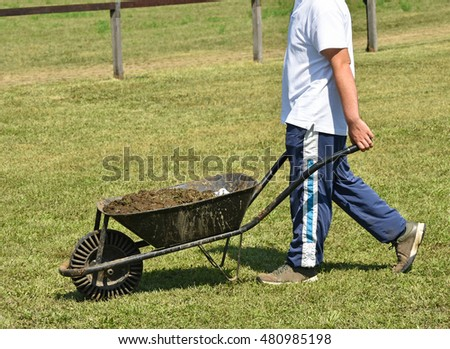 Man with wheelbarrow full of manure outdoors