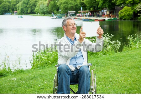 Man with wheelchair and tablet PC in the park - stock photo