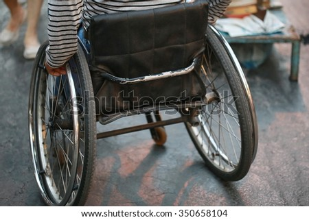 man with wheelchair move on road, Thailand - stock photo
