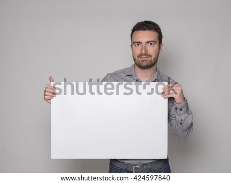 man with white banner cardboard isolated on gray background - stock photo