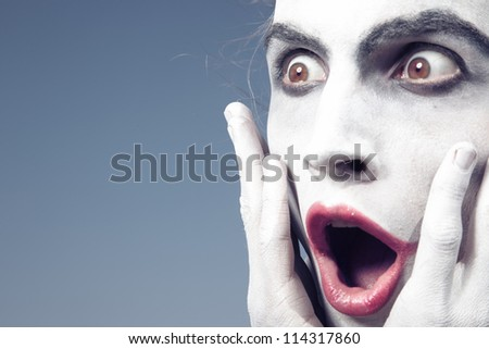 Man with white makeup expressing shock